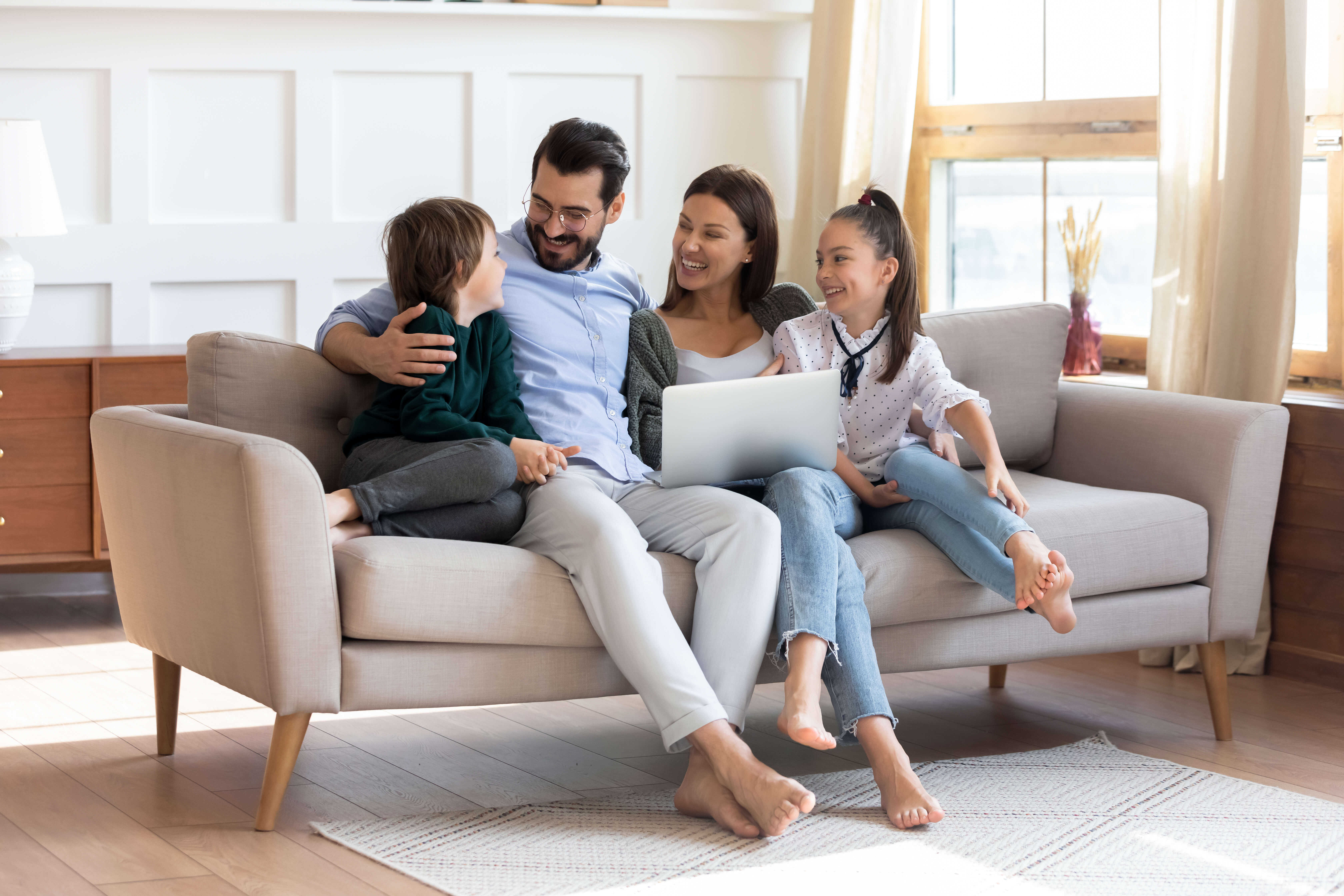 Family of four watching movie on laptop